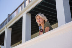 Thoughtful woman holding white wine glass in balcony at restaurant Royalty Free Stock Photography