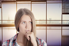Thoughtful woman in interior with city view Royalty Free Stock Photography