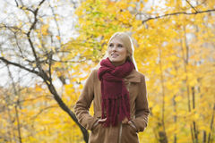 Thoughtful woman in jacket looking away at park during autumn Stock Images