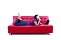 Thoughtful woman with laptop on couch Stock Photos