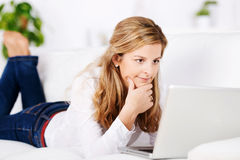 Thoughtful Woman With Laptop On Sofa Royalty Free Stock Photos