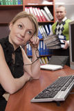 Thoughtful woman leaning on desktop Stock Images