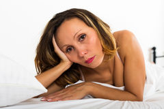 Thoughtful woman lies  in bedroom. Portrait of thoughtful woman with downcast eyes in bedroom Stock Images