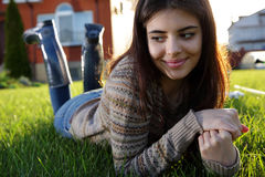 Thoughtful woman lies on the lawn stock images