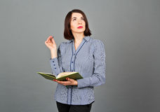 Thoughtful woman looking away while thinking. Write on her notes Royalty Free Stock Photo