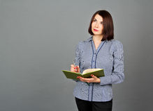 Thoughtful woman looking away while thinking. Write on her notes Stock Photos