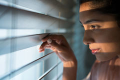 Thoughtful woman looking through window blinds. Close-up of thoughtful young woman looking through window blinds Stock Photo