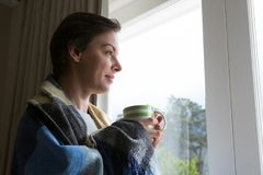 Thoughtful woman looking through window while having cup of coffee. At home Stock Images