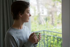 Thoughtful woman looking through window while having cup of coffee. At home Stock Photos