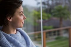 Thoughtful woman looking through window Royalty Free Stock Images