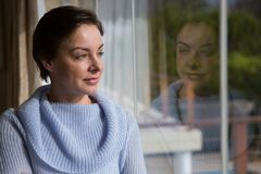 Thoughtful woman looking through window Royalty Free Stock Image