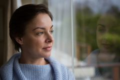 Thoughtful woman looking through window Royalty Free Stock Photo