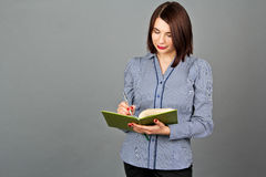 Thoughtful woman looking and writing on her notes. Stock Photos