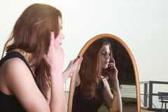 Thoughtful woman looks at the reflection in mirror Royalty Free Stock Photo