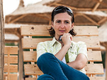 Thoughtful woman lounge chair on beach Stock Images