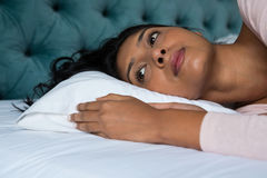 Thoughtful woman lying on bed. Thoughtful woman lying down on bed at home Royalty Free Stock Photography