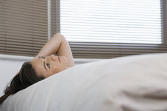 Thoughtful Woman Lying In Bed Stock Photo