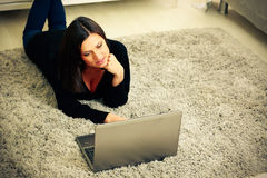 Thoughtful woman lying on the carpet with laptop Stock Photos