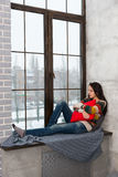 Thoughtful woman lying down on the windowsill hugging a pillow a Royalty Free Stock Images