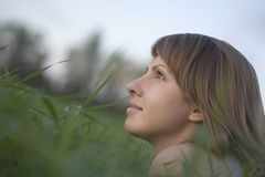 Thoughtful Woman Lying On Grass Royalty Free Stock Photography