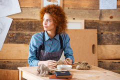 Thoughtful woman making sculpture with clay in pottery workshop. Thoughtful curly young woman sitting in pottery workshop and making sculpture with clay Royalty Free Stock Images
