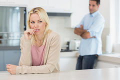 Thoughtful woman with man standing in background at kitchen Stock Image