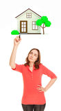 Thoughtful woman with marker drawing house Stock Image