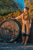 Thoughtful woman near wooden barrel in outdoors Royalty Free Stock Image
