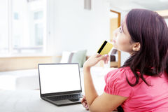 Thoughtful woman online shopping at home Royalty Free Stock Image