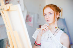 Thoughtful woman painter standing in front of easel with paintbrush Stock Image