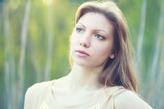 Thoughtful woman in the park Royalty Free Stock Image