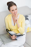 Thoughtful woman with personal organizer and laptop Royalty Free Stock Image