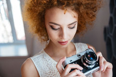 Thoughtful woman photographer holding vintage camera Royalty Free Stock Photo