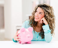 Thoughtful woman with a piggybank Stock Images
