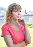Thoughtful woman in a pink shirt outside Royalty Free Stock Photos