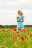 Thoughtful woman in poppy field Stock Photos