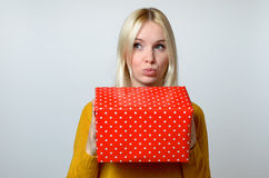 Thoughtful Woman with Pouting Lips Holding Present Royalty Free Stock Photography