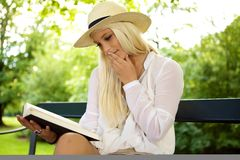 Thoughtful woman reading a book. In a green park Royalty Free Stock Image