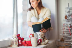 Thoughtful woman reading book in christmas decorated home Stock Photography