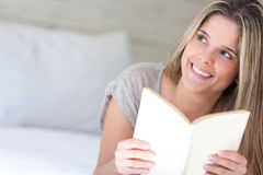 Thoughtful woman reading a book Stock Images