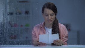 Thoughtful woman reading letter behind rainy window, having nostalgic memories. Stock footage stock video footage