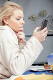 Thoughtful woman reading a mobile phone message Stock Photo