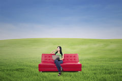 Thoughtful woman on red sofa at green field Royalty Free Stock Images