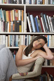Thoughtful Woman Relaxing Against Bookshelves Royalty Free Stock Image