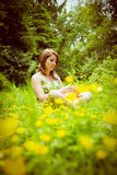 Thoughtful woman relaxing in field Stock Photo