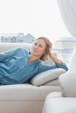 Thoughtful woman relaxing on her couch Stock Image
