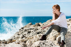 Thoughtful woman relaxing at the sea Stock Image