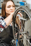 Thoughtful woman repairing the wheel bicycle in the garage. Dreams about better life. Thoughtful charming meditative woman sitting in the garage and repairing Stock Images