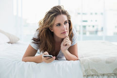 Thoughtful woman resting in bed. Using phone Royalty Free Stock Photos