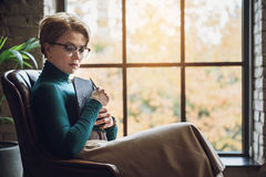 Thoughtful woman in room afore window Royalty Free Stock Photo